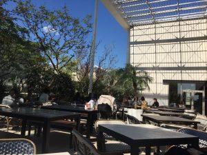 ビルの屋上にお客さんがくつろげるイスとテーブルが並んだオシャレなテラス