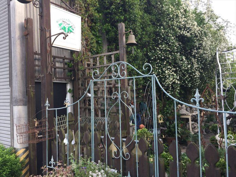 鉄の扉と木製のフェンスと看板がある園芸店の入り口