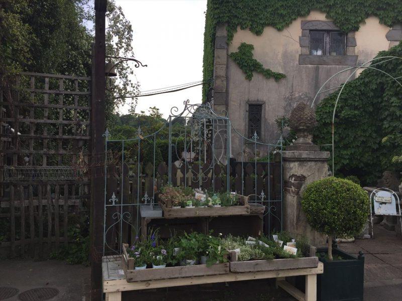 洋風の建物とアイアンフェンスの外に置かれた植物の販売棚