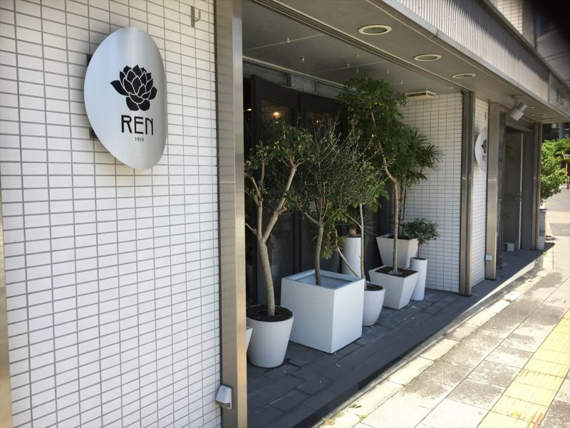 白いタイルのビルの1階にある観葉植物専門店『REN』のお店とその看板