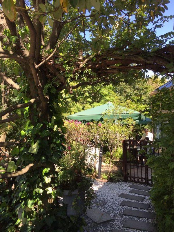 奥にカフェの緑のテントが見える砂利と敷板のガーデン入り口