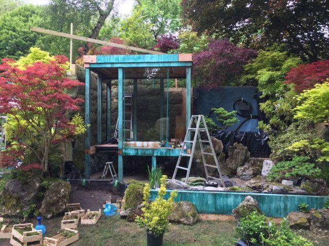 緑青の建屋の周りに緑が植栽されている庭園