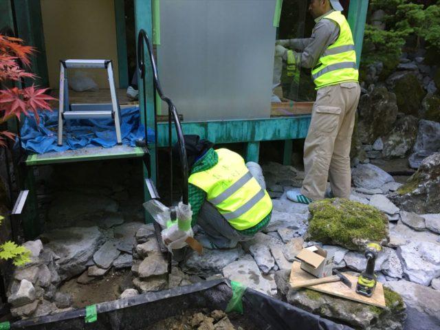 緑青のの建屋の下の敷石を設置する職人