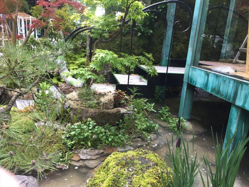 緑青の建物へ続くアイアンの手すりがあるガラスと石の階段