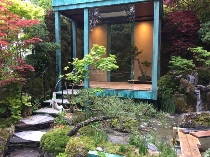 和風の庭の中に建つ明かりがともされた緑青の建物