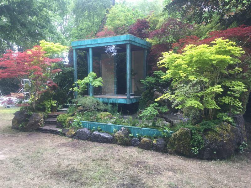 緑青の建屋と木々で覆われた庭