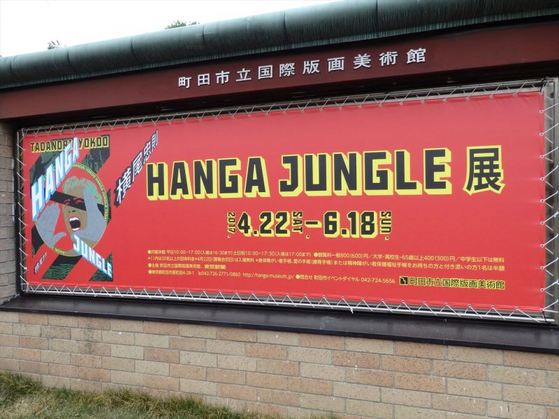 町田市立国際版画美術館の案内板に赤い下地で『hangajungle展』と黒のゴシック体で書かれた案内ポスター