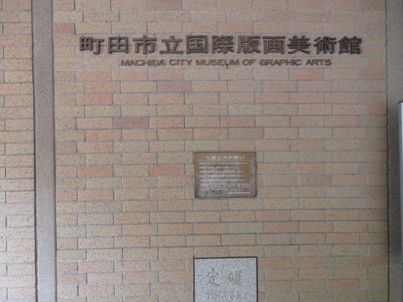 『町田市立国際版画美術館』と記されたレンガの壁