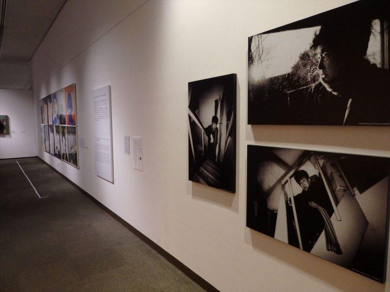 白の壁に男性のモノクロ写真が展示されている