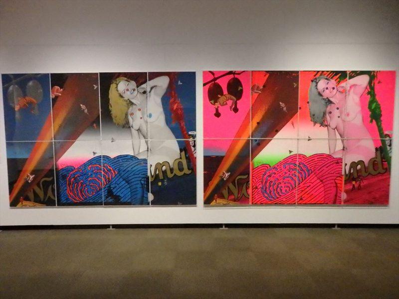 白の壁に展示された南国で上半身裸体の女性がポーズをとっている八枚一組の絵画が色違いで二種類