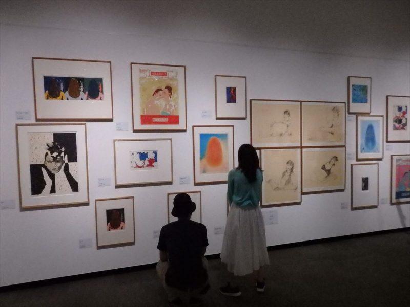 白の壁にランダムに並べられたさまざまな絵画