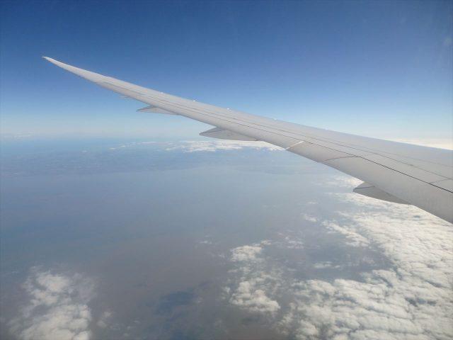 雲の上の青い空を飛んでいるジャンボジェット機の左ウィング