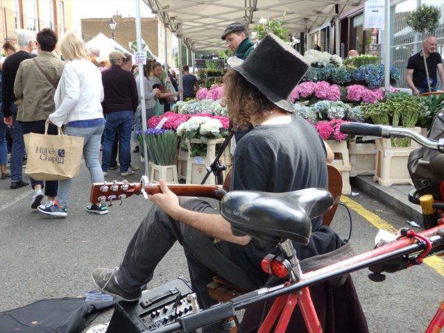 ロンドンの花市で音楽を奏でるストリートミュージシャン