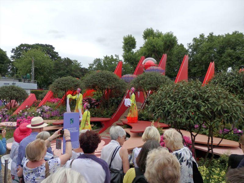 中国風の衣装を着たパフォーマーと赤いパネルが立ち並ぶ巨大な庭
