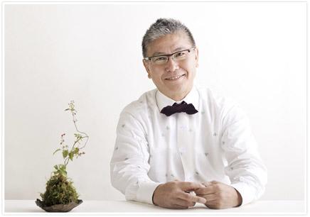 白をバックに苔の鉢と白い洋服を着た男性