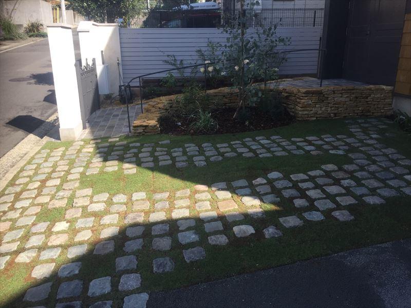 ベルギー産の石と芝、ポーラス舗装の駐車場