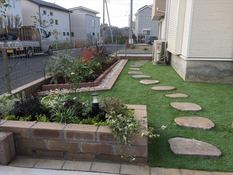 プロが作った人工芝とレンガの花壇と自然石の飛び石があるお庭