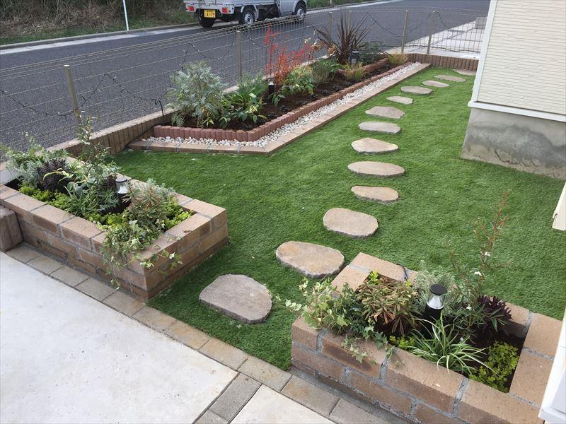 人工芝と自然石の飛石、レンガの花壇がプロの技術で綺麗に施工