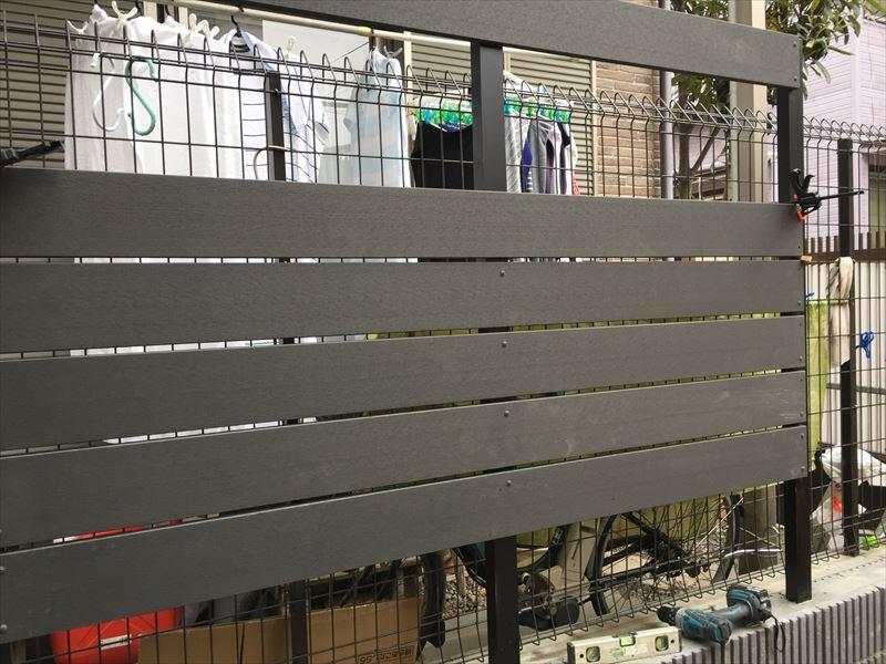 施工途中の高さ1m50cmのアルミ支柱と樹脂の人工木