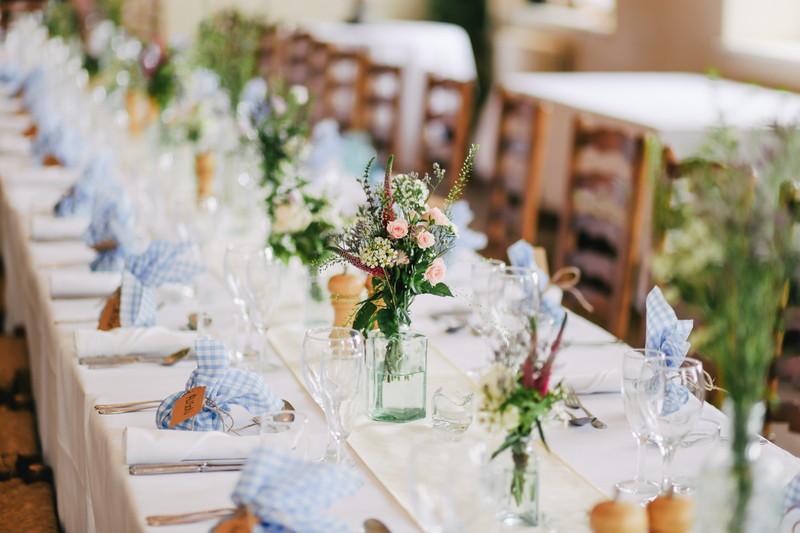 長テーブルにクロスと食器とセンターピースの花がある画像
