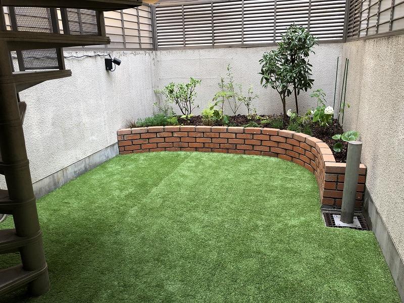 完工したレンガ花壇と人工芝と植栽とガーデンライトの