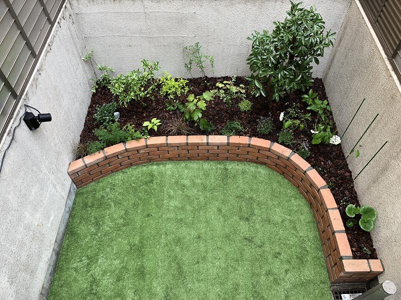 成長を見越して隙間を空けて植栽したレンガの花壇