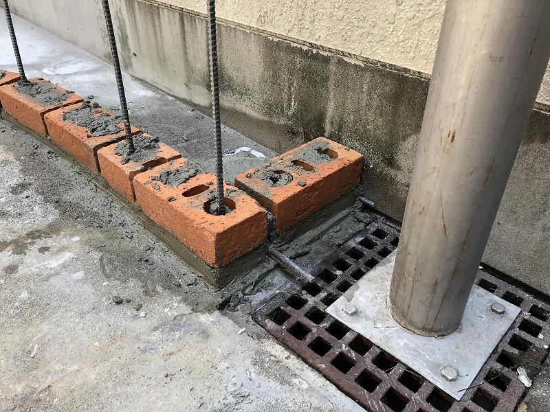 排水マスの近くレンガには水抜き穴をつくってあるナチュラルガーデンのレンガの花壇の施工