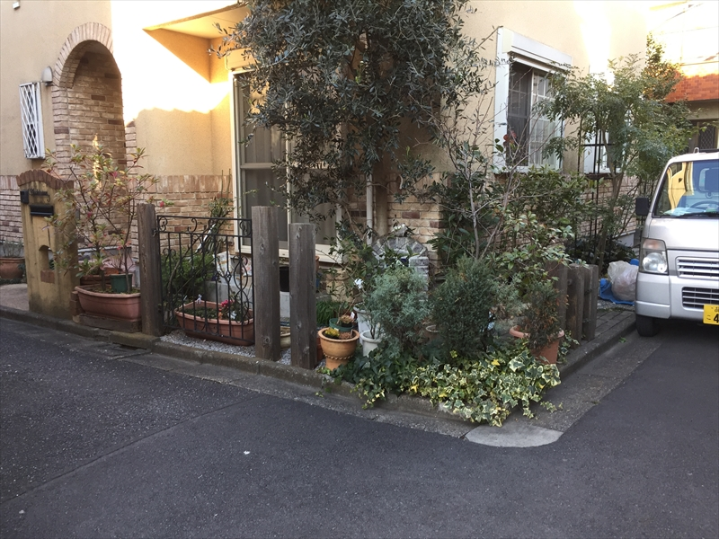 朽ちかけの枕木と色あせた門柱と荒れた植物