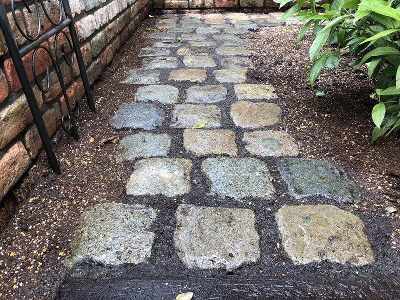 植物が育つ固定したアンティークストーンの石畳