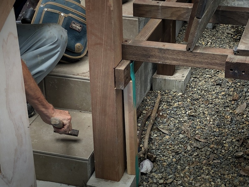 新しいパーゴラの柱を既存のウッドデッキに合わせる作業する職人