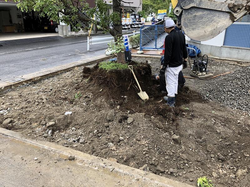 足立区の中央本町耳鼻咽喉科で植木周りの土を鋤き取る作業員