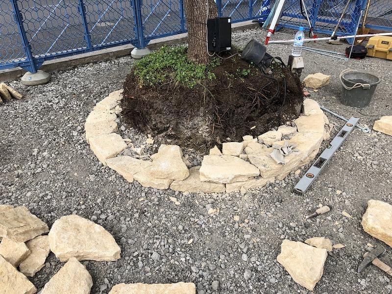 一段目が積み終わって二段目の石積みが行われている円形の花壇
