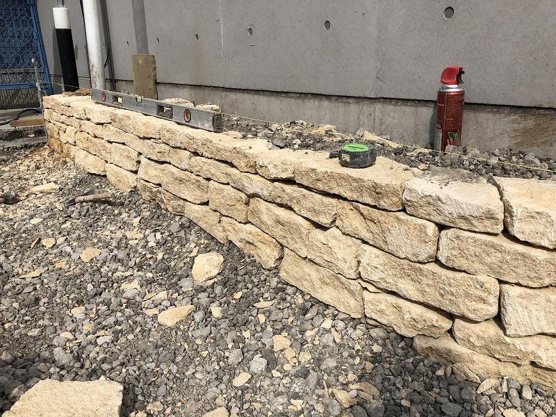 水平を確認しながら施工がすすむイギリスのコッツウォルズ地方のハニーストーンの直線的花壇