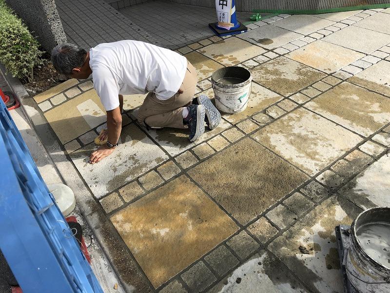 はみ出したモルタルを綺麗に掃除する石張り職人さん