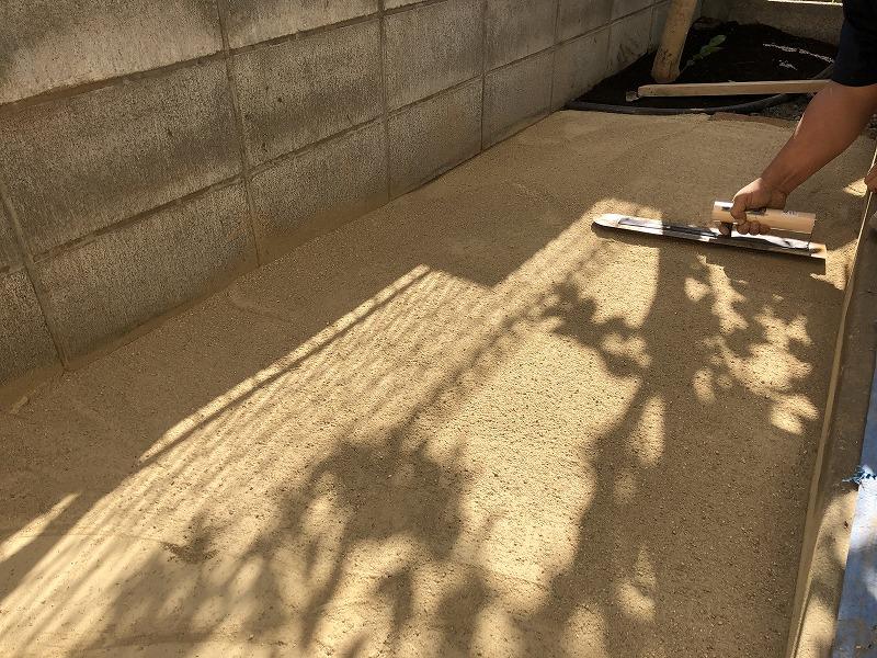 左官道具を使って固まる土をならす施工方法