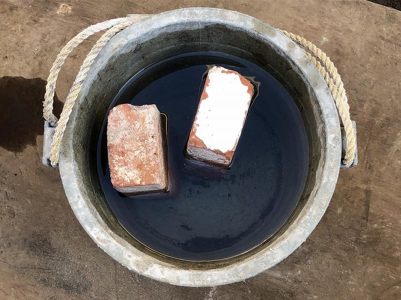 水を張ったバケツにレンガを浸してレンガを濡らす