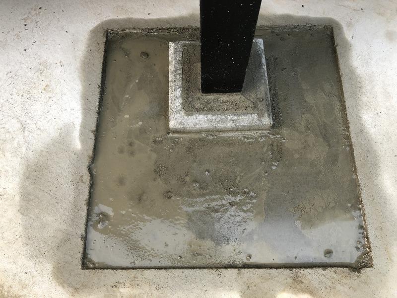 支柱のために斫った穴をふさぐセメント作業
