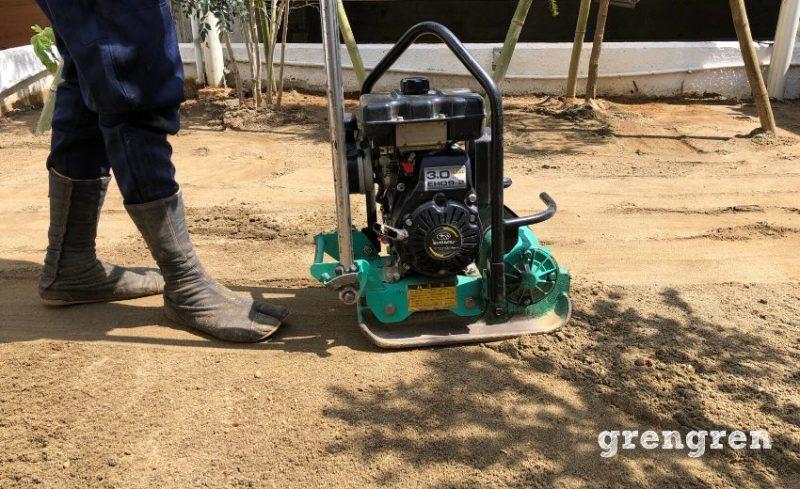 芝生を敷くために山砂を撒いてプレートコンパクターで固める作業