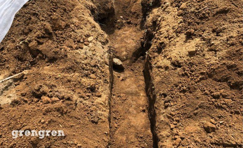 芝生を張る前に水はけを良くするための透水管を埋める作業