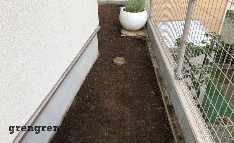 芝生から自然石のステップを設置するための地面の調整が終わったお庭