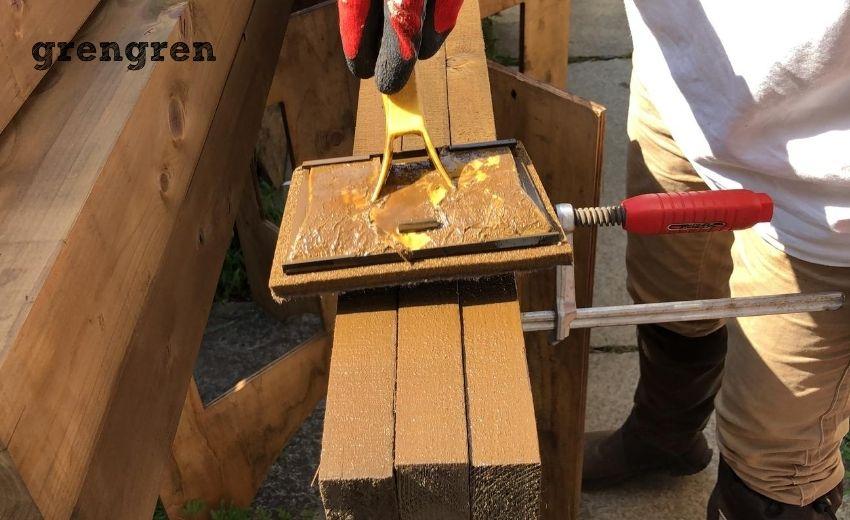 ウッドフェンスの笠木の材木を三枚一度に塗っていく作業