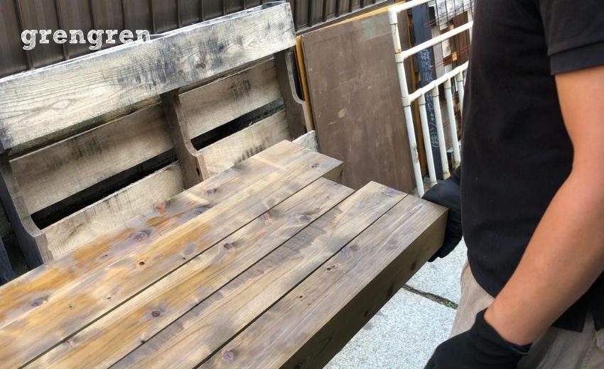 ウッドフェンスやウッドデッキのための油性キシラデコールを塗装するのに材木をひっくり返す様子