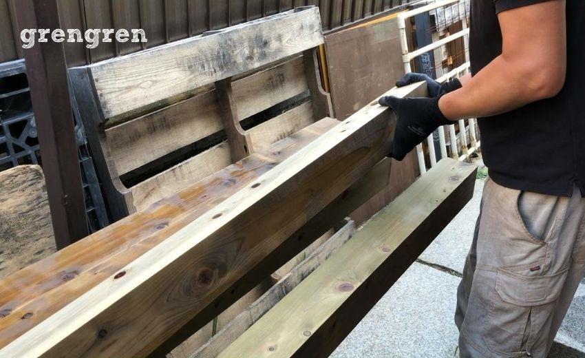 塗装のために材木を回転させる作業