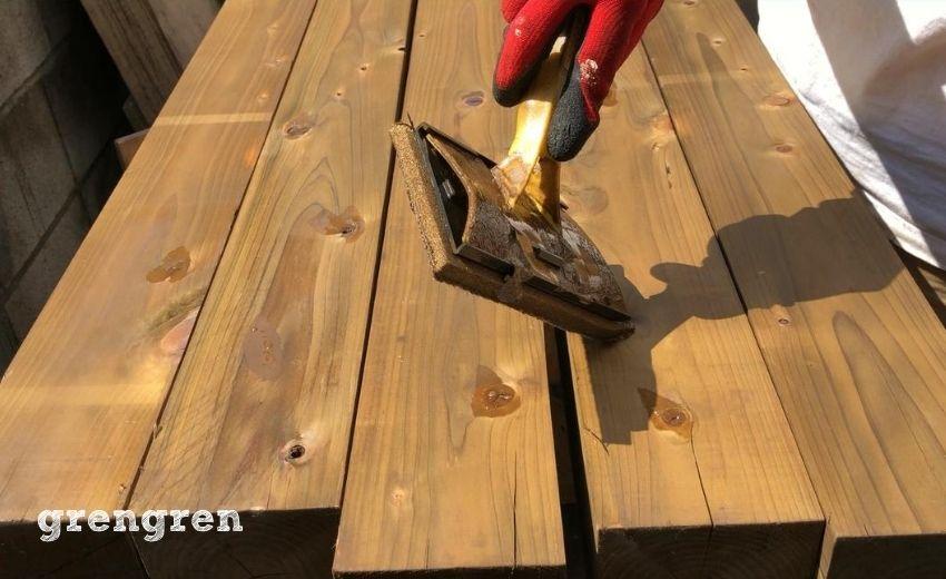 ウッドフェンスの塗装で材木の節の奥まで塗る作業