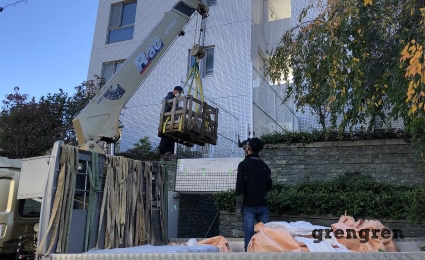 クレーンでマンションの2階の搬入を行う作業