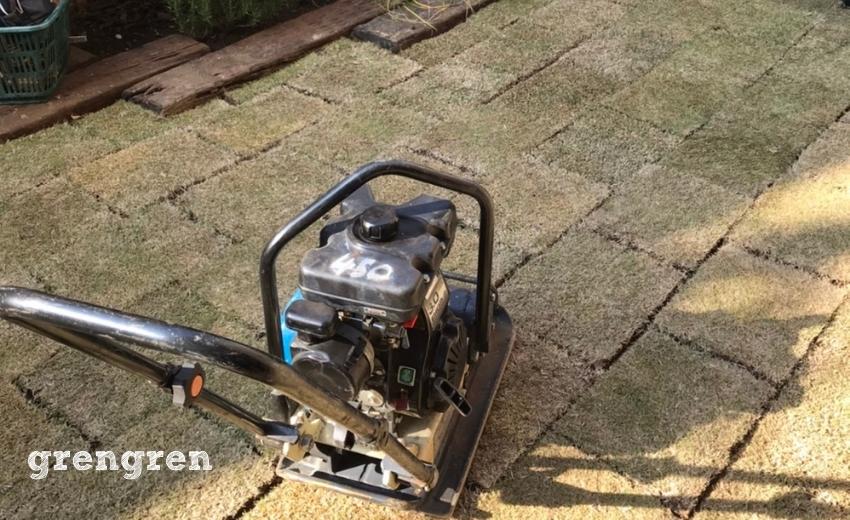芝生と地面を密着させるために重機プレートをかける
