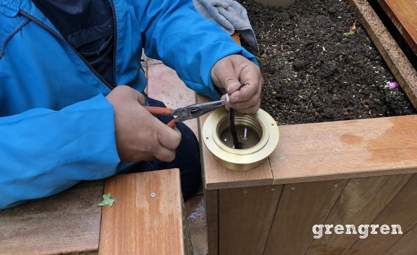 世田谷ローズガーデンの庭づくりでガーデンライトを接続する職人