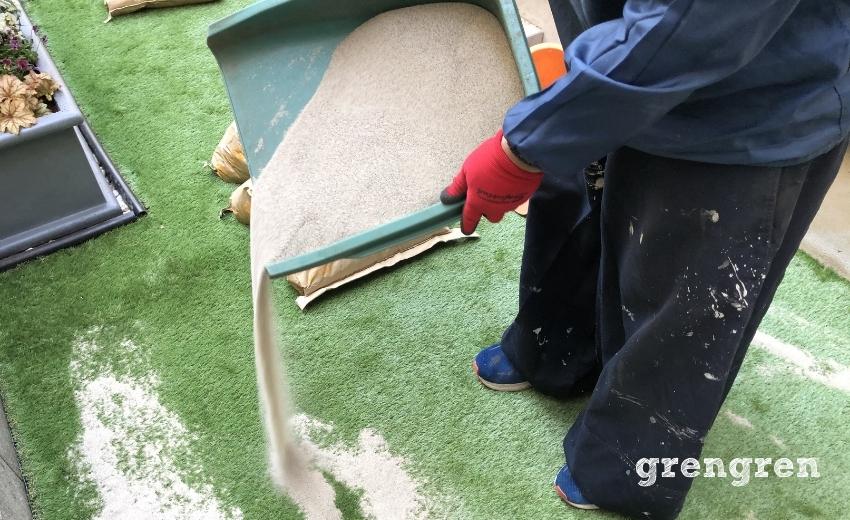 人工芝の施工のための珪砂を撒く作業