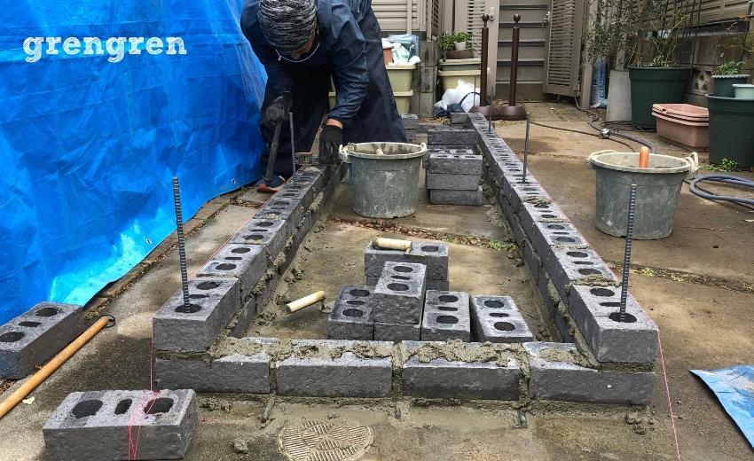 中野区で花壇作成のために段目のレンガを積む作業