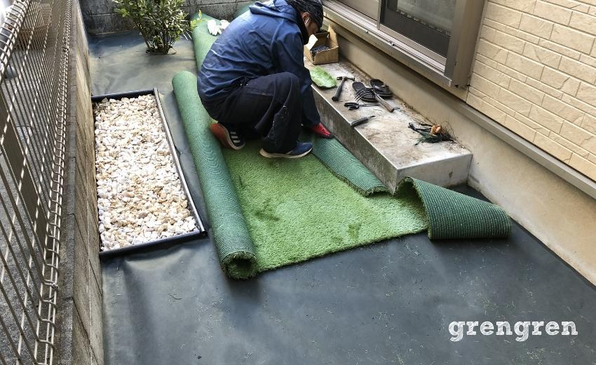 調布市の庭で人工芝を施工する職人